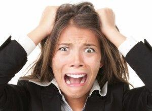 жінка тримається за голову і кричить